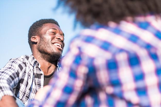Le jeune homme afro noir rit beaucoup en plein air