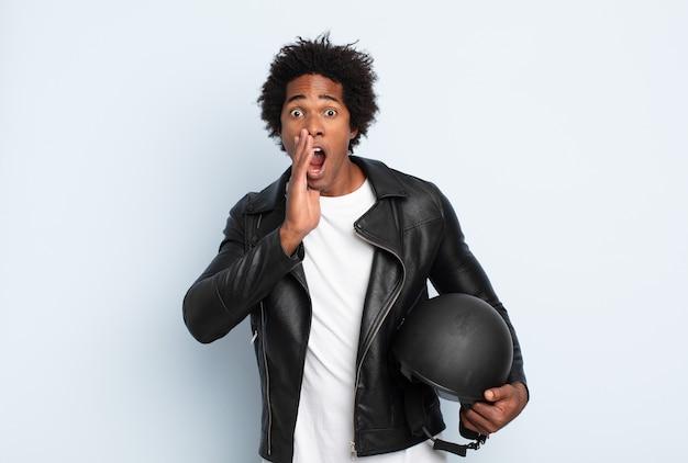 Jeune homme afro noir se sentant choqué et effrayé, l'air terrifié avec la bouche ouverte et les mains sur les joues