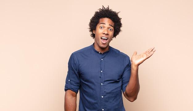 Jeune homme afro noir se sentant choqué, étonné et surpris, montrant son approbation en faisant bien signe avec les deux mains
