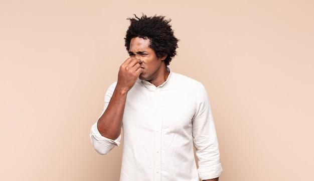 Jeune homme afro noir se sentant dégoûté, tenant le nez pour éviter de sentir une odeur nauséabonde et désagréable