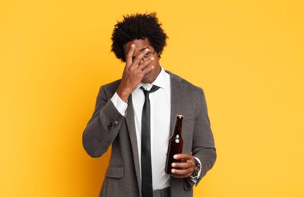 Jeune homme afro noir se sentant ennuyé, frustré et somnolent après une tâche fastidieuse, ennuyeuse et fastidieuse, tenant le visage avec la main
