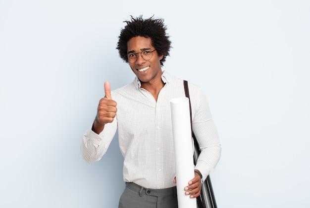 Jeune homme afro noir se sentant fier, insouciant, confiant et heureux, souriant positivement avec les pouces vers le haut