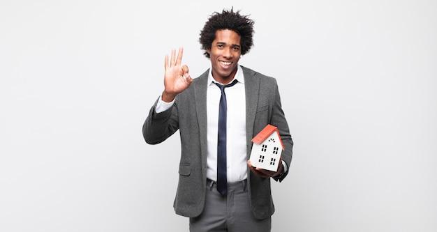 Jeune homme afro noir se sentant heureux, détendu et satisfait, montrant son approbation avec un geste correct, souriant