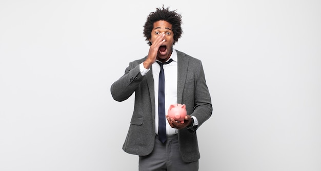 Jeune homme afro noir se sentant heureux, excité et positif, donnant un grand cri avec les mains à côté de la bouche, appelant