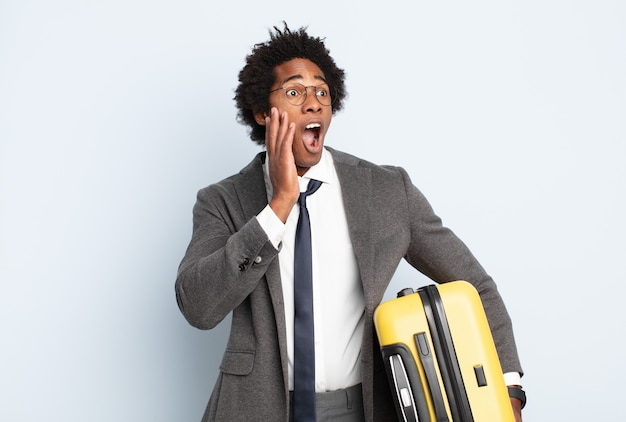 Jeune homme afro noir se sentant heureux, excité et surpris, regardant sur le côté avec les deux mains sur le visage