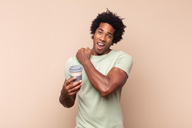 Jeune homme afro noir se sentant heureux, positif et prospère, motivé face à un défi ou célébrant de bons résultats
