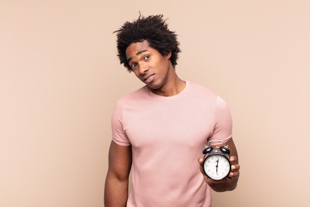 Jeune homme afro noir se sentant perplexe et confus, avec une expression stupide et stupéfaite en regardant quelque chose d'inattendu