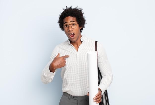 Jeune homme afro noir semblant choqué et surpris avec la bouche grande ouverte, pointant vers lui-même