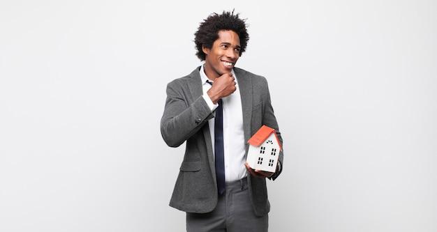 Jeune homme afro noir souriant avec une expression heureuse et confiante avec la main sur le menton, se demandant et regardant sur le côté