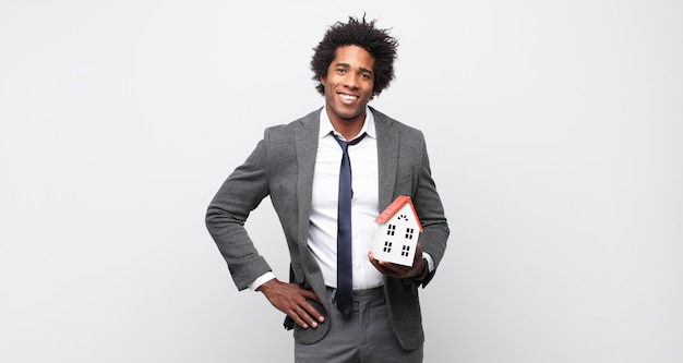Jeune homme afro noir souriant joyeusement avec une main sur la hanche et une attitude confiante, positive, fière et amicale
