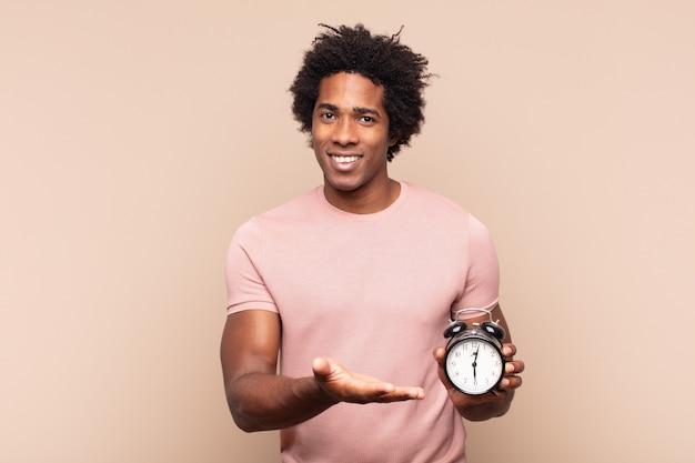 Jeune homme afro noir souriant joyeusement, se sentant heureux et montrant un concept dans l'espace de copie avec la paume de la main