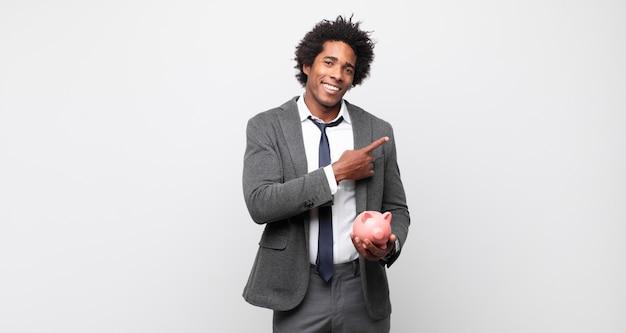 Jeune homme afro noir souriant joyeusement, se sentant heureux et pointant vers le côté et vers le haut, montrant l'objet dans l'espace de copie