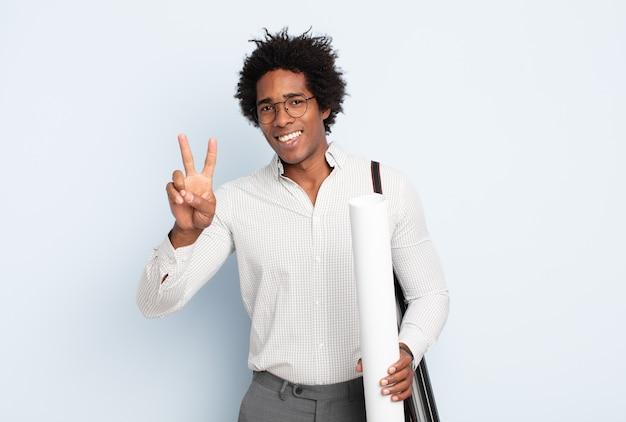 Jeune homme afro noir souriant et regardant heureux, insouciant et positif, gesticulant la victoire ou la paix d'une seule main