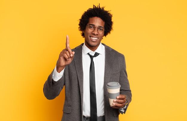 Jeune homme afro noir souriant et à la sympathique, montrant le numéro un ou d'abord avec la main en avant, compte à rebours