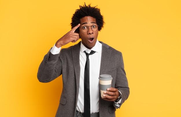 Jeune homme afro noir à la surprise, la bouche ouverte, choqué, réalisant une nouvelle pensée, idée ou concept