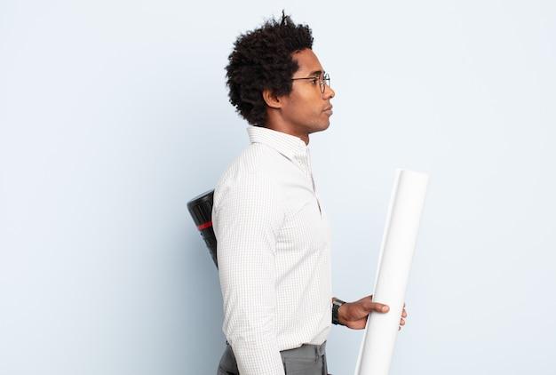 Jeune homme afro noir sur la vue de profil à la recherche de copier l'espace à venir, penser, imaginer ou rêver