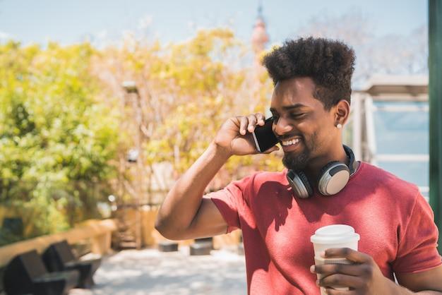 Jeune homme afro parlant au téléphone.