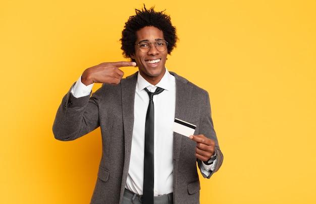 Jeune homme afro souriant pointant avec confiance vers son propre large sourire, attitude positive, détendue et satisfaite