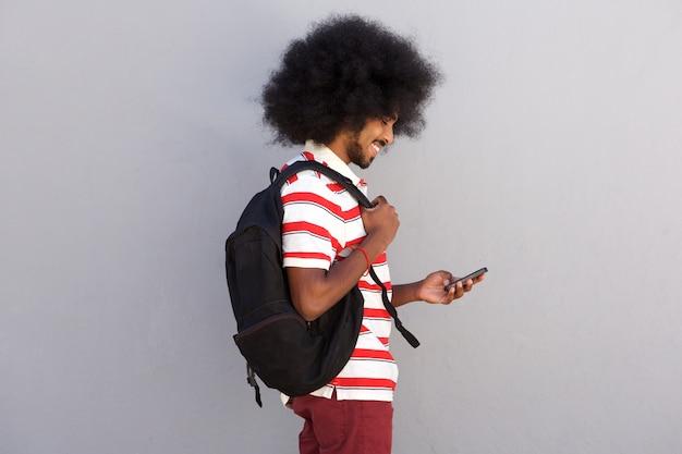 Jeune homme avec afro et téléphone portable souriant