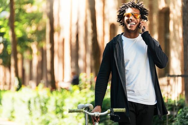 Jeune homme afro utilisant un téléphone portable et un vélo à pignon fixe dans la rue.