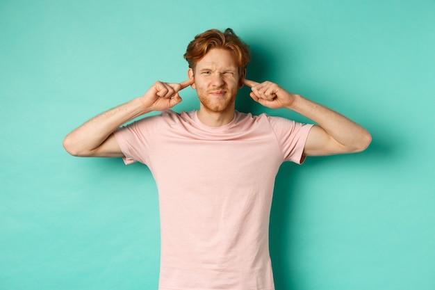 Jeune homme agacé aux cheveux roux et à la barbe ferma ses oreilles et grimaça, dérangé par un son fort dérangeant, des voisins bruyants, debout sur fond turquoise