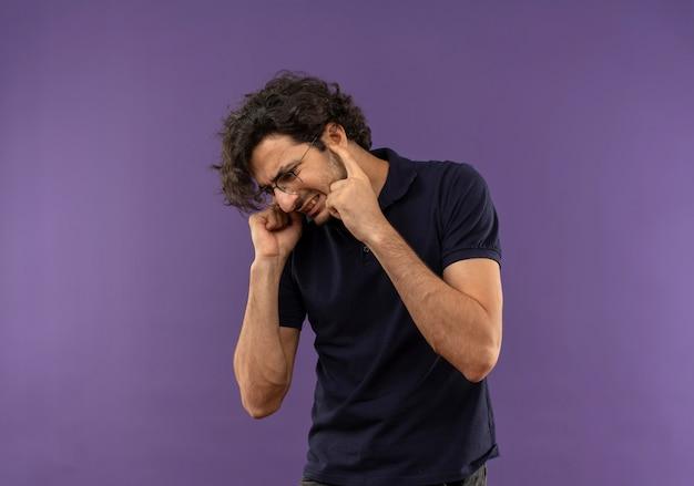 Jeune homme agacé en chemise noire avec des lunettes optiques parle au téléphone et ferme l'oreille avec le doigt isolé sur le mur violet