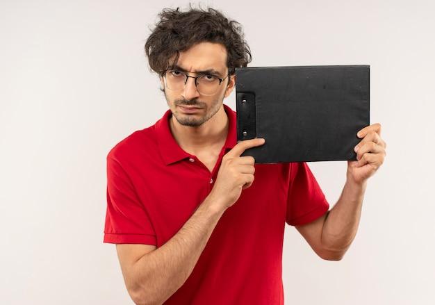 Jeune homme agacé en chemise rouge avec des lunettes optiques détient le presse-papiers et semble isolé sur un mur blanc