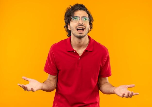Jeune homme agacé en chemise rouge avec des lunettes optiques tient les mains ouvertes isolé sur mur orange