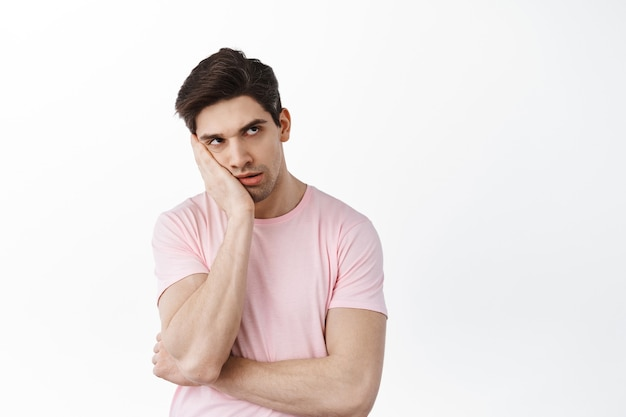 Un jeune homme agacé et ennuyé roule des yeux et soupire, se penche sur la main avec une expression indifférente et insouciante, debout irrité contre un mur blanc