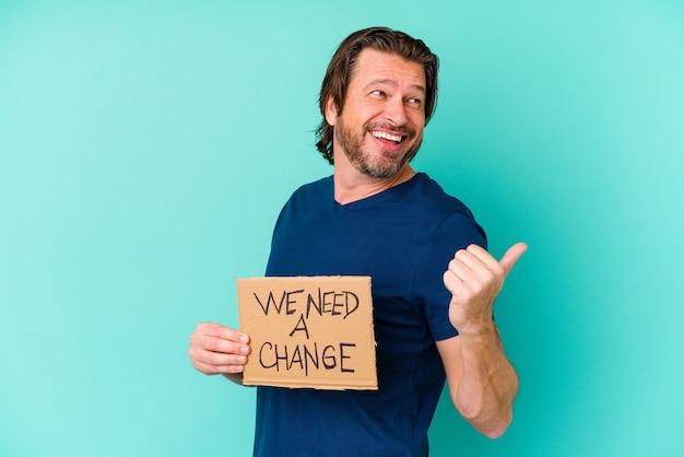 Jeune homme d'âge moyen de race blanche tenant un nous avons besoin d'une pancarte de changement sur bleu