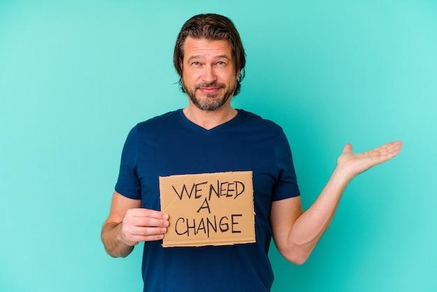 Jeune homme d'âge moyen de race blanche tenant un nous avons besoin d'une pancarte de changement isolé sur mur bleu