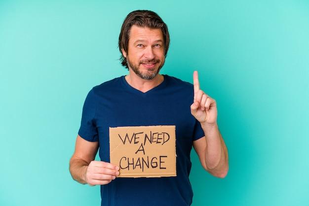 Jeune homme d'âge moyen de race blanche tenant un nous avons besoin d'une pancarte de changement isolée sur bleu