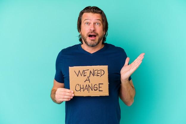 Jeune homme d'âge moyen tenant un nous avons besoin d'une pancarte de changement isolé sur mur bleu