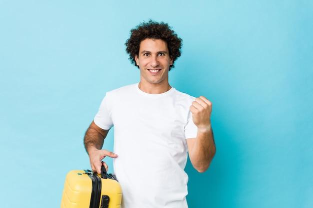 Jeune homme d'âge moyen tenant une valise acclamant sans soucis et excité. concept de victoire.