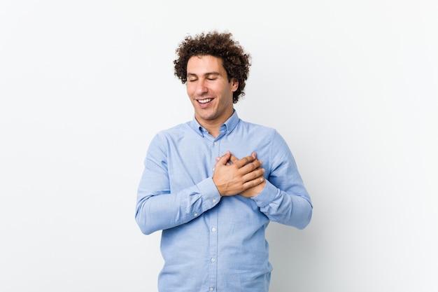 Jeune homme d'âge mûr bouclé portant une chemise élégante en riant en gardant les mains sur le cœur