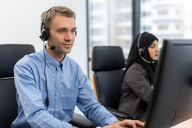Jeune homme agent du service client avec des casques travaillant sur ordinateur dans un centre d'appels, parler avec le client pour aider à résoudre le problème avec son esprit de service