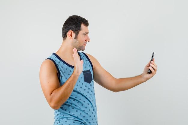 Jeune homme agitant la main sur le chat vidéo en maillot bleu, vue de face.