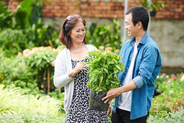 Jeune homme aidant le client à trouver les meilleures fleurs dans un centre de jardinage