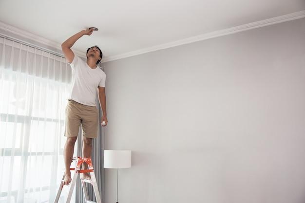 Jeune homme à l'aide d'un escalier pour installer des lumières dans le salon à la maison