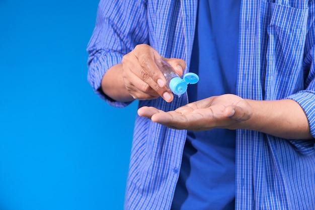 Jeune homme à l'aide de gel désinfectant pour prévenir les virus
