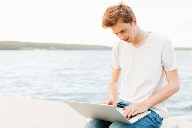 Jeune homme à l'aide d'un ordinateur portable au bord de l'eau