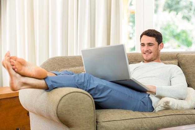 Jeune homme à l'aide d'un ordinateur portable sur un canapé dans le salon