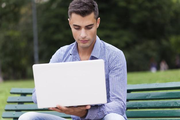 Jeune homme à l'aide d'un ordinateur portable à l'extérieur