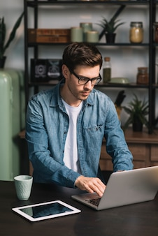 Jeune homme à l'aide d'un ordinateur portable avec une tasse de café et une tablette numérique sur le comptoir de la cuisine