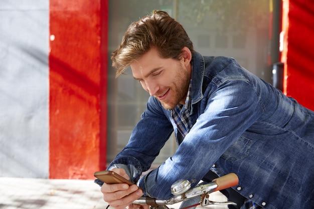 Jeune homme à l'aide de smartphone dans un vélo