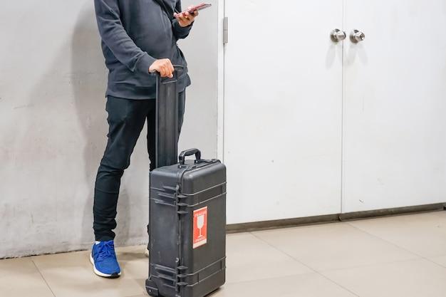 Jeune homme à l'aide de smartphones avec ses bagages à la vérification de vol dans les aéroports