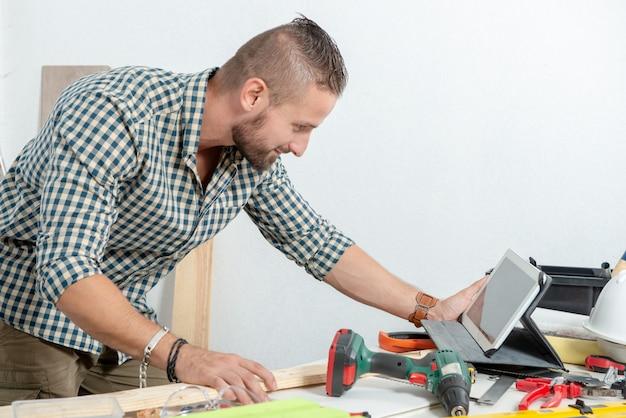 Jeune homme à l'aide d'une tablette pour bricoler à la maison