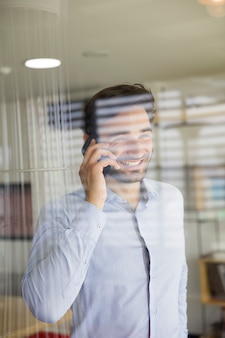 Jeune homme à l'aide d'un téléphone portable derrière la vitre au bureau