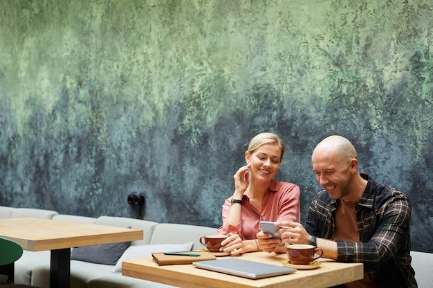 Jeune homme à l'aide de téléphone portable tout en buvant du café au café avec sa petite amie