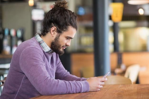 Jeune homme à l'aide de téléphones mobiles au restaurant